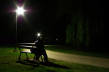 lonely man sitting on a bench in the park at night