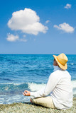 man with hat meditation in the beach poster