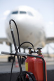 fire extinguisher and a white airliner in the background poster