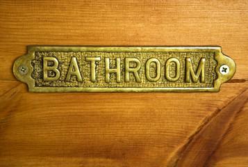 A bronze bathroom sign on a wooden bathroom door.