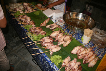 barbecued squids on stick at thai bazaar