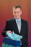 Man in business suit carrying a gift bag poster