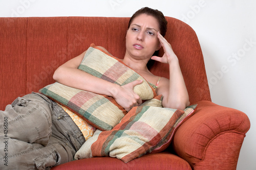 Woman have headache and laying on sofa