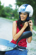 beautiful happy young girl with helmet on motorcycle