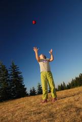 girl throwing red apple in air