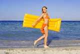happy smiling woman strolling on seashore with lilo,airbed  poster
