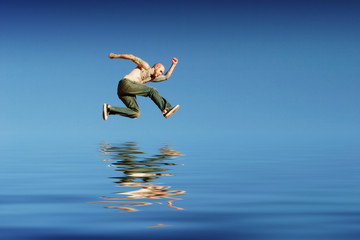 Athletic man jumping on water