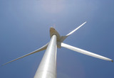 wind mill power generator against blue sky with lens flare poster
