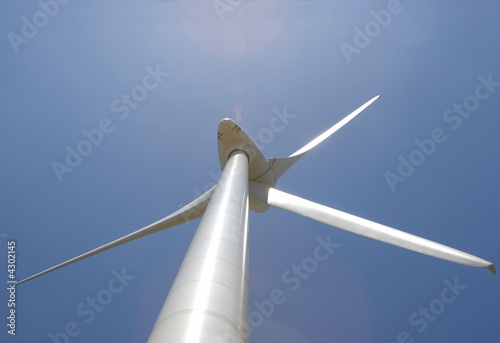 poster of wind mill power generator against blue sky with lens flare