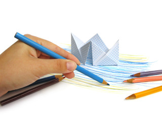 Paper ship on drawing sea background with hand holding a pencil