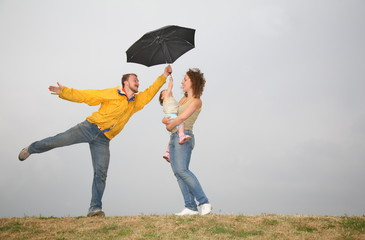 fun family with umbrella against a gray sky