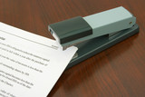 Office stapler and document on wooden background poster