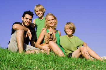 happy young family with pet dog outdoors