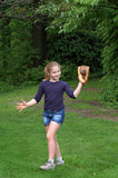 Girl catching baseball outside in yard poster