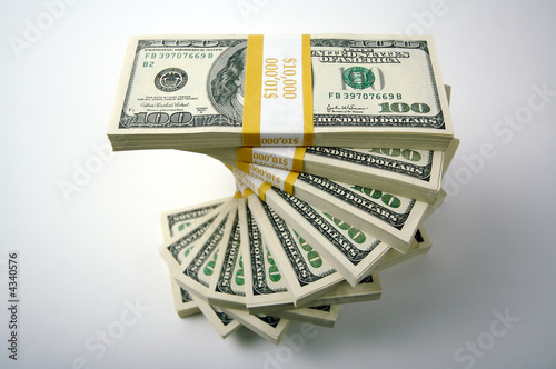 Spiraling Stacks of Hundred Dollar Bills on a white background.