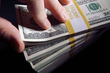 Stacks of One Hundred Dollar Bills on a Black Background.