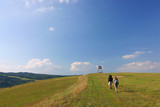 hikers on the meadow under blue sky poster