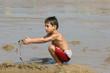 petit garçon seul entrain de jouer sur le sable