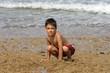 petit garçon accroupi sur la plage