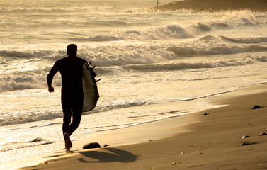 Surfer running towards the waves at sunset.
