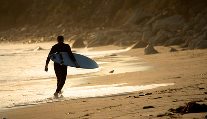 Surfer walking at the beach during sunset