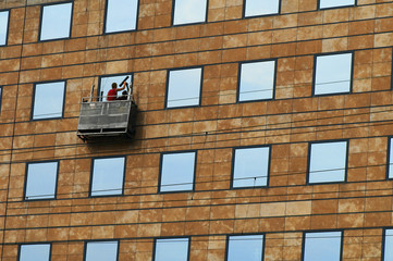 Photo of process of washing of windows at the big height.