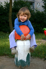 Girl on playground clambering on huge mushroom