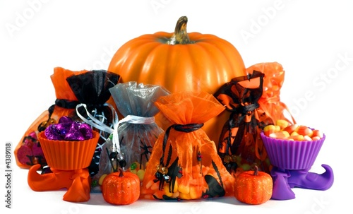 treat bags with candy sitting in front of a pumpkin