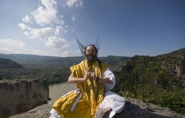 Gelber Mönch betet auf einem windigen Felsen