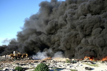Bulldozer taming out of control fire of tyres at a tip site
