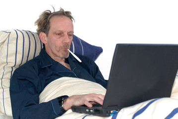 sick in bed with laptop.
