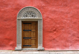 Carved Medieval Door in the Red Stucco Wall poster