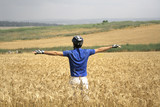 cyclist standing up in a hay field poster