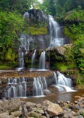 Big waterfall through dense forest