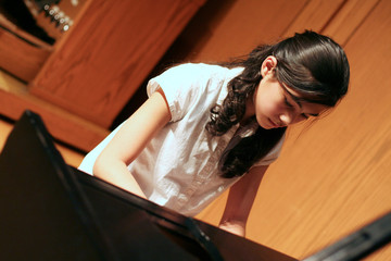 Young teen girl playing the grand piano