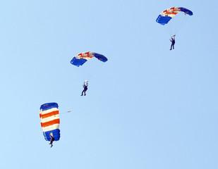 Three parachutists landing at an  airshow