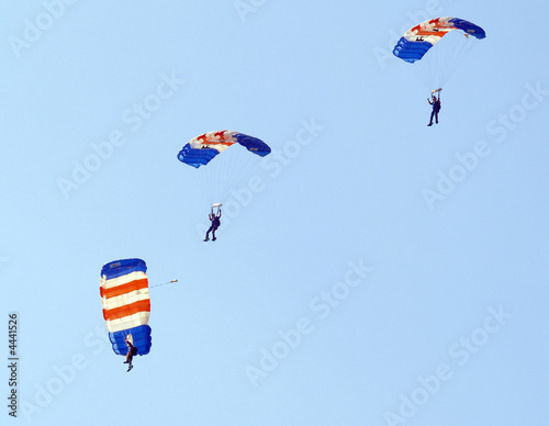Three parachutists landing at an  airshow
