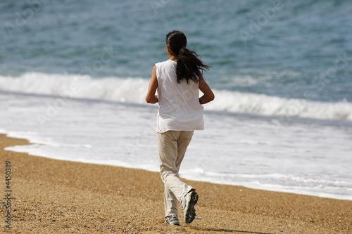 belle femme qui court au bord de l'eau