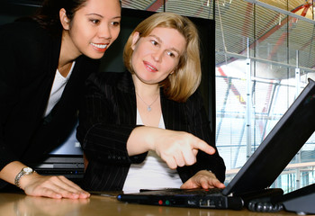 Two female businesswoman, both looking at the laptop