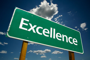 """""""Excellence"""" Road Sign with dramatic clouds and sky."""