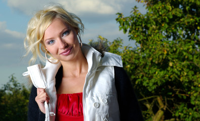 Beautiful young blond woman , Sky and green background.