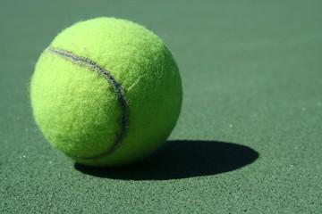 A Tennis ball on a green court