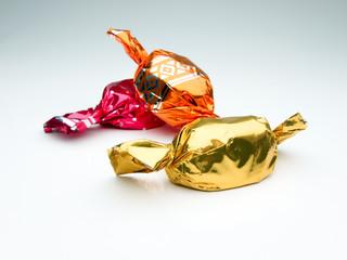 bonbons in roter, goldenener, oranger einwickelfolie