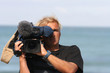 homme entrain de filmer avec une caméra professionnelle