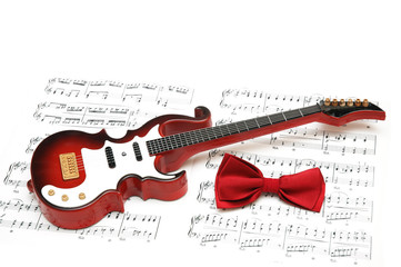 Musical notes, guitar and bow tie on white