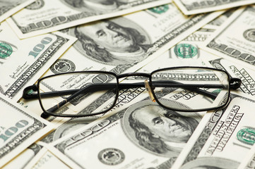 Reading glasses over the dollar bank notes