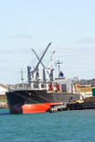 Cargo ship docked at wharf poster