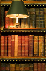 Lots of old books on a bookshelf with lamp in library.