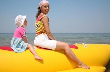 Mother with daughter  siting on the inflatable boat