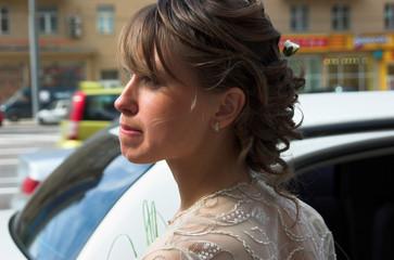 Elegance bride with a flower bouquet near the car
